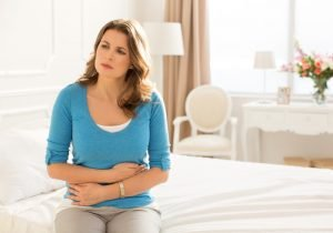 Mid-age woman sitting on bed and holding hands on her stomach.